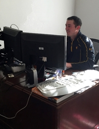 Josh Becker sits at his desk and writes code for programs for Handel Information Technologies.