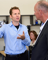 Jeff Clune (left) discusses his research with Wyoming Gov. Matt Mead.