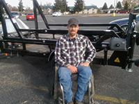 WDH President Corey McGregor in front of the adaptive hunting trailer built by a CEAS student team.