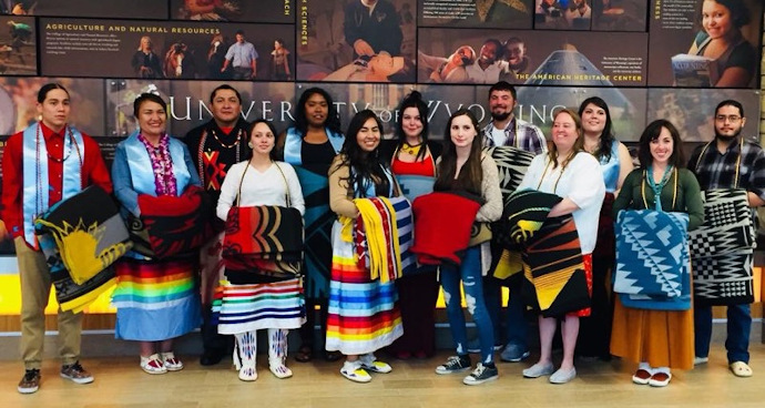 a group of graduates with native design blankets