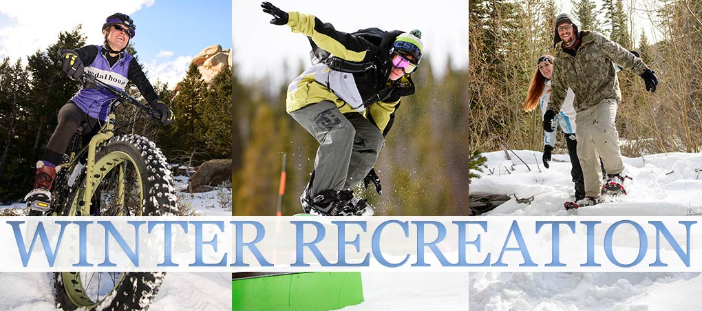 Girl riding bike in the mountains during winter, snowboarder and two people snow shoeing