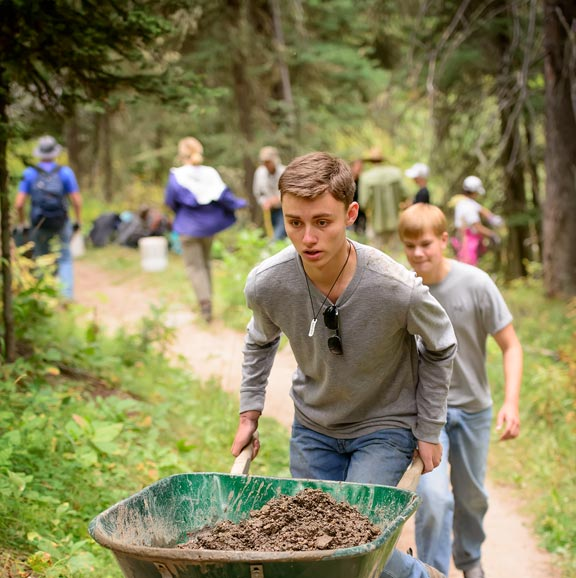 Picture of students moving wheel barrows of dirt