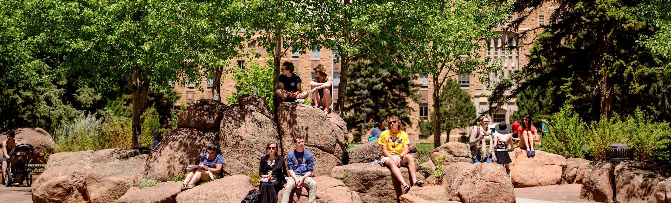 Several people relaxing on an outdoor plaza on campus in the summer time