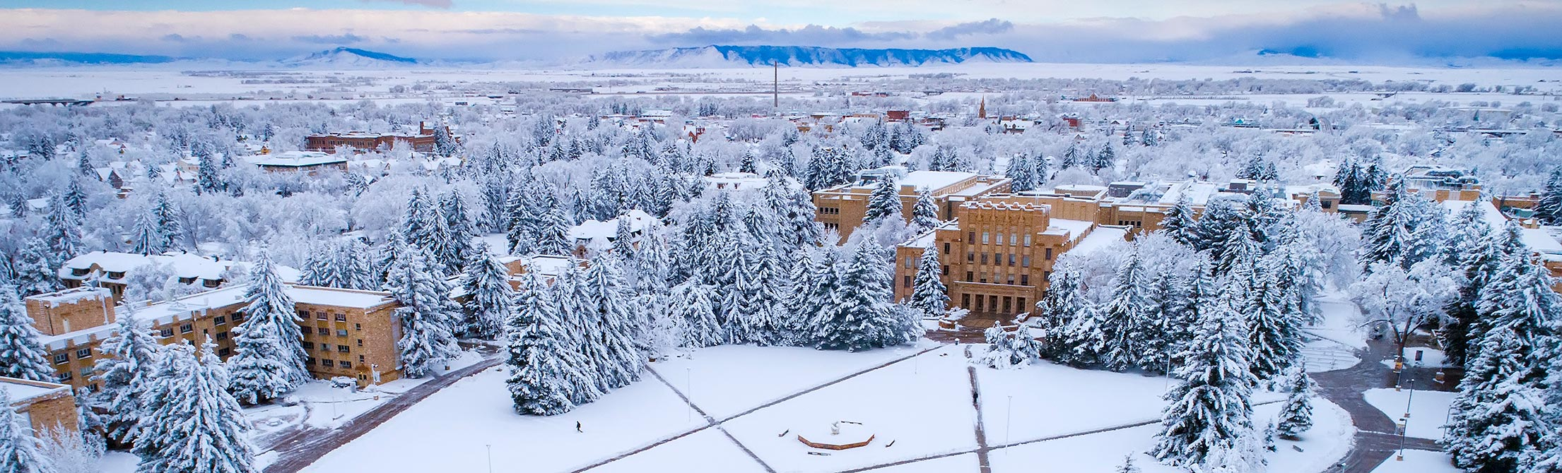 Aerial view of the University of Wyoming campus during winter with snow blanketing the buildings, trees, and ground