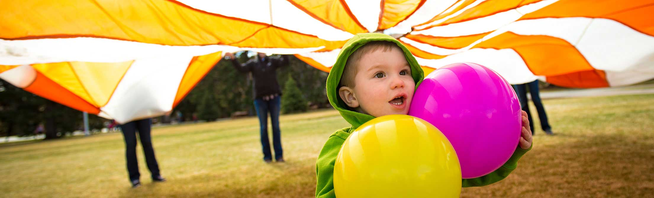 young child holding balloons and wearing a green jacket stands underneath an orange and white parachute