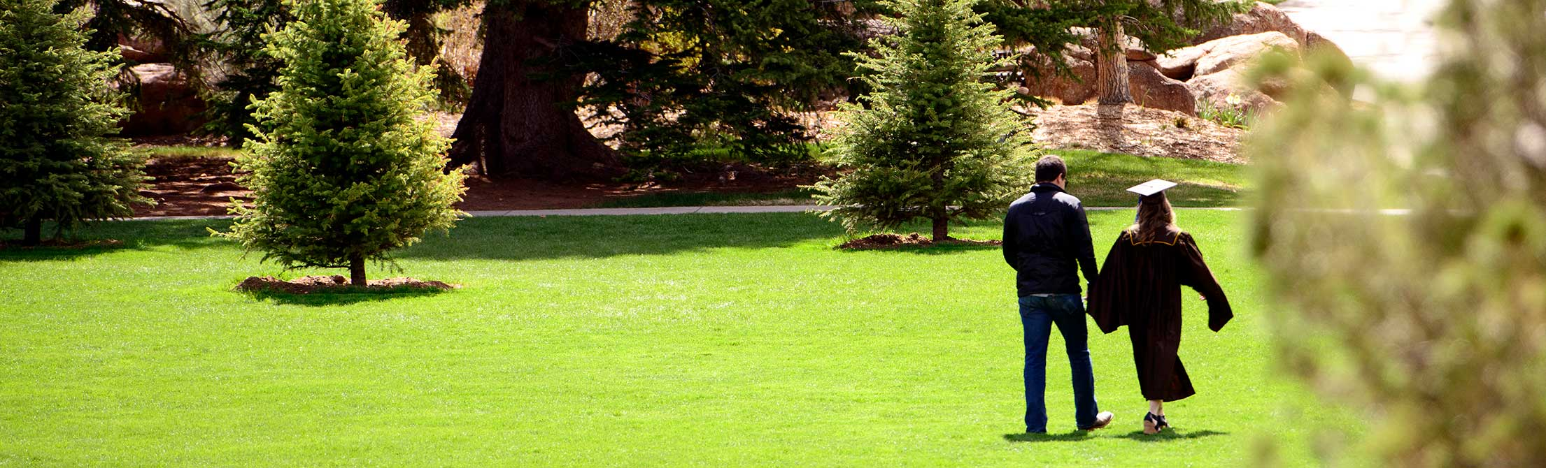 Two graduates walking on a grassy field