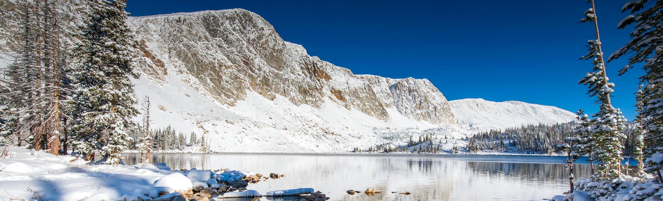 Photograph of Medicine Bow Peak in winter with lake at base of mountain