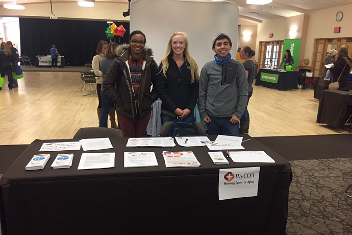 A photo of three research assistants working at a University Health Fair