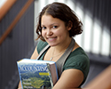 Image of accounting student holding her book in the stairwell