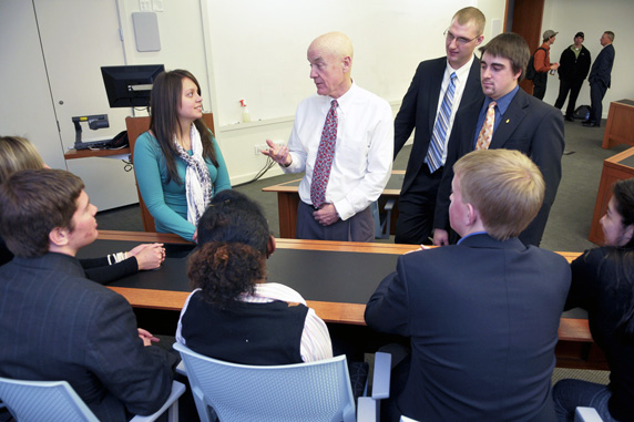 Image of Dick McGinity speaking with students in a classroom