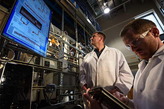 Jonathan Brant, center, analyzes water data with graduate student Coleman Henry, right, in his lab.