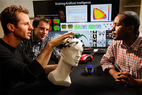 Jeff Clune, left, explains artificial-intelligence applications to graduate students.