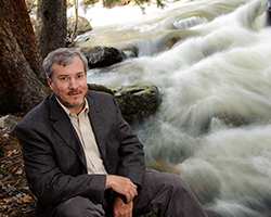 UW Professor Fred Ogden poses by a stream for a portrait.