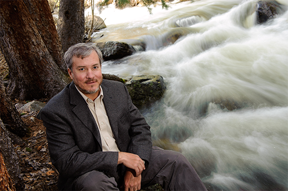 UW Professor Fred Ogden poses for a portrait near a stream.