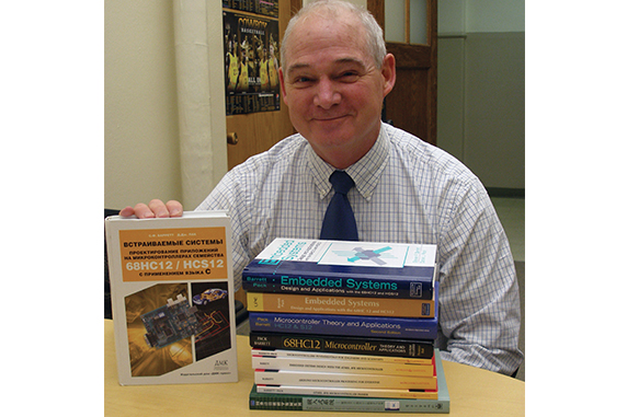 Steve Barrett poses for a portrait with some of his published books.