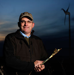 Jonathan Naughton poses for a portrait near a wind turbine.