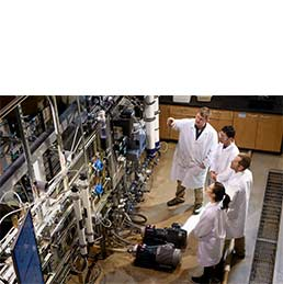 Group of people in lab coats in engineering lab