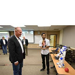 Electrical engineering student Vivaswat Shastry demonstrates the capabilities of a NAO robot with Wyoming Gov. Matt Mead on a 2016 visit to the College of Engineering.