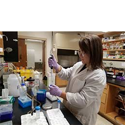 Woman in lab using syringe and beakers