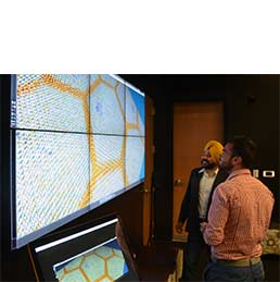 Two men view diagrams on large TV display