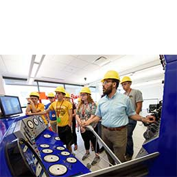 People wear hard hats in drilling simulator space for demonstration
