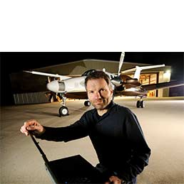 man with a laptop computer in front of an airplane