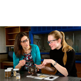 Two women discuss biomass materials in a mechanical engineering lab