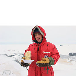 Man holds frozen bowl of spaghetti in Anarctica