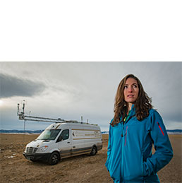 Woman poses for photo with atmospheric science vehicle