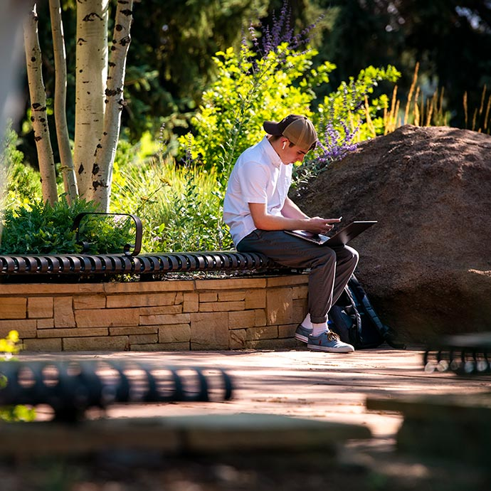 student on bench studying