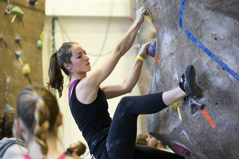 A female student climbs on the climbing wall in Half Acre Gym