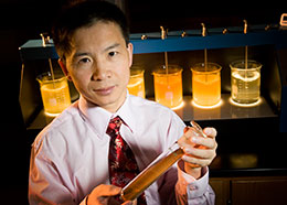 man holding large test tube in lab