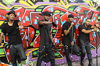 four men performing in front of graffiti background