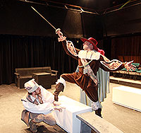 two men in costume - one is crouching and one waves a sword