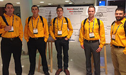 five men in yellow shirts standing in front of a display board