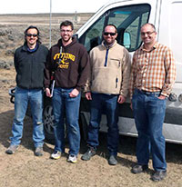 four men standing in front of a van