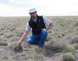 man kneeling in the middle of the prairie