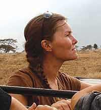 head portrait of woman against background of African plains and trees