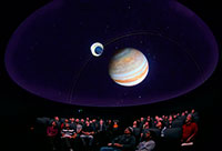group of people watching planetarium show, with planets shown above them