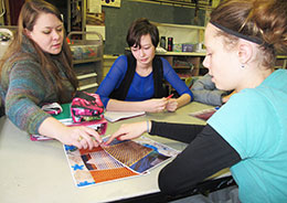three people at a table looking at colored patterns in the middle of the table