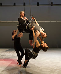 four people using harnesses and wires for vertical dance