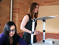 one woman sitting and one standing at a portable podium set on a table
