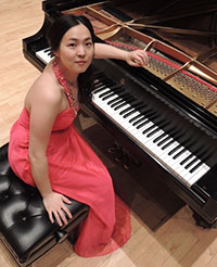 woman sitting at grand piano