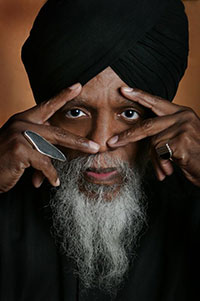 head portrait of man wearing a turban and framing his eyes with his fingers