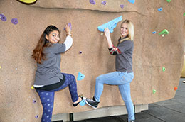 two women posing as if climbing rock climbing wall