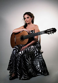 woman seated and holding a guitar