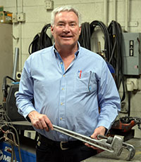 man in workshop holding a large pipe wrench