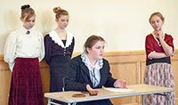 four middle school girls dressed in historical costumes