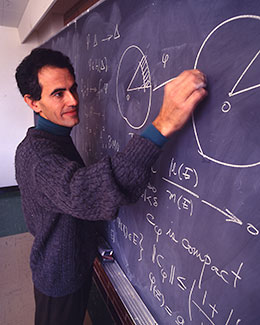 man writing mathmatical symbols on a chalkboard