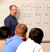 man standing at whiteboard with students watching